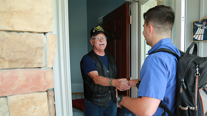 A Dobbs Heating and Air employee greeting a customer art their front door.